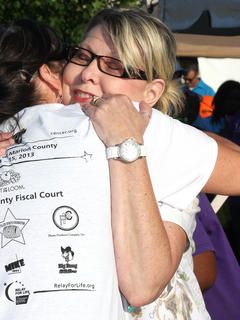 Breast cancer survivor Patsy Myers hugs one of the Relay for Life committee members after receiving her survivor medallion.