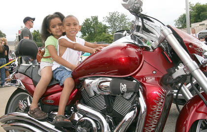 India Young, 5, holds on to the back of Donovan Drury, 4, before the ride begins.