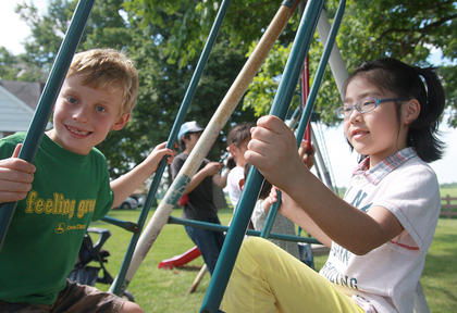 Wyatt Thomas Mattingly, 7, and Yuna Gorie share a swing.
