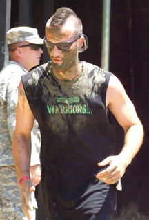 A muddy racer keeps running after finishing the Vertical Limit.