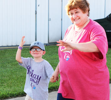 Relay for Life Chairperson Lisa Sandusky and nephew Ethan Gootee wave during a lap at Relay for Life.