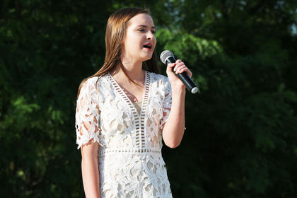 Abi Adams sings the National Anthem before the survivors' ceremony begins at the Marion County/Washington County Relay for Life on June 23.