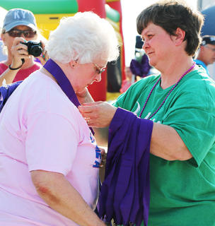 Carolyn Luckett receives her survivor's medal from Stephanie Buckman.