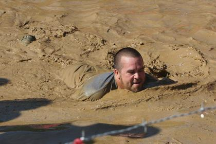 "Chad ""Little Beno"" Spalding swims through the Muddy Mayhem obstacle during Saturday's Warrior Dash."