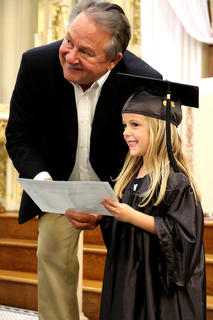 St. Augustine Grade School Principal Paul Terrell gives Elle Rogers, 4, her diploma and they pose for a photo together.