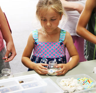 Heartlyn Dorroh makes a memory jar with sand, rocks and shells.