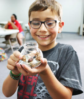 Ty Johnson smiles proudly with his nature rocks memory jar.