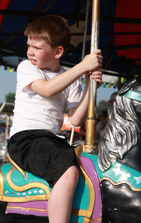 Patrick Simpson, 7, takes in the sights as he spins around the merry-go-round.