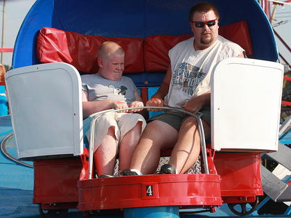 Justin Royse (11), left, and his uncle Tracey Royse go for a spin on the Tilt-O-Whirl on July 2.
