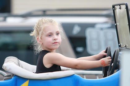 Olivia Spalding, 3, goes for a spin in an old jalopy.