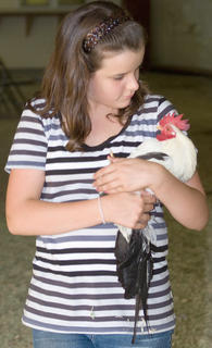 Kaylee Beed gives her bird a motherly look as she brings it to its home cage.