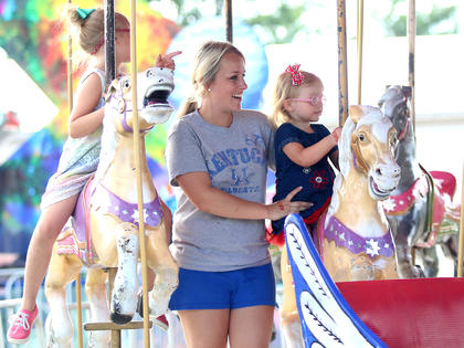 Bailey Miles (center) and her daughters, Laci Miles and Lexi Miles (not pictured), enjoy a ride on the merry-go-round at the Marion County Fair July 3.