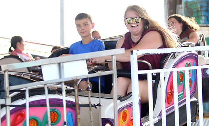 Michael Cobb (left) and Aleea Routt take a ride on the Musical Express at the Marion County Fair July 3.