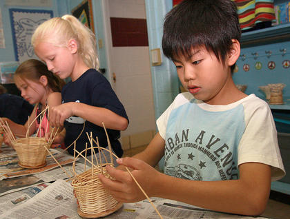 Masaya Jinno makes a basket. Aubrey Knopp (center) and Sarah Wise (left) work on their own baskets in the background.
