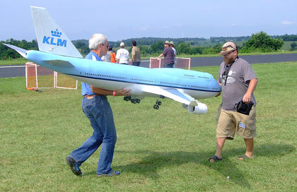 Willem Degraaf holds up an electric jet as Chris Degraaf checks something before taking it out for a flight. The Degraafs of Hanson built the jet themselves and painted it to match a plane used by KLM, which is the Royal Dutch Airlines.