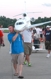 David Payne of Champaign, Ill, helps Ali Machinky carry his Falcon 7-X back to the hangar after a flight Friday evening.