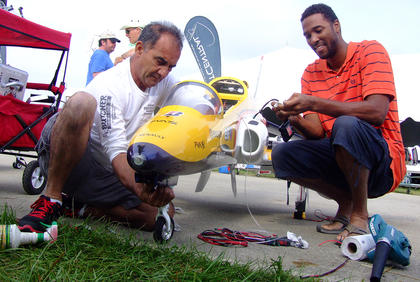 Luke Martinez, left, of Fort Lauderdale, Fla., assists Lawrence Collie of the Bahamas as Collie gets his plane ready for a flight on Saturday.