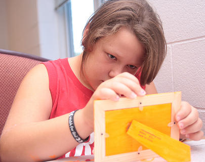 Leslie Gammon, 11, takes a closer look at the frame she designed to hold a manipulated photograph she created during the camp.