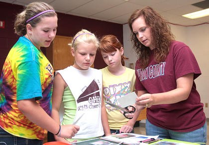 Technology instructor Jennifer Russell shows an example of manipulated photography to (from left) Laney Hall, Taylor Leake and Olivia Lee.