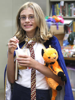 "Cassandra Thomas, 11, of Lebanon smiles as she holds a cup full of ""Butterbeer"". The drink was made of butter, butterscotch topping, ice cream and cream soda. Thomas dressed as Hermione, complete with a copy of ""Tales of Beedle the Bard"" and cat, Crookshanks."