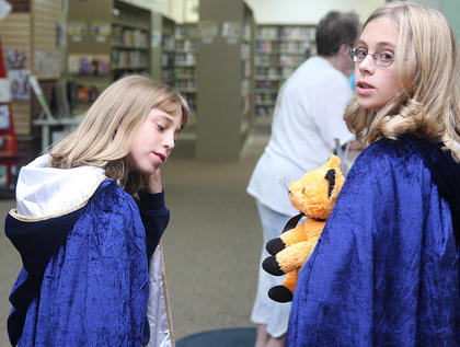 Jessica Thomas, 9, and Cassandra Thomas, survey the scene as they wait for the Harry Potter party at the public library to begin.