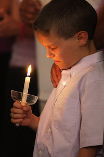 Austin Tingle, 8, holds a candle and closes his eyes in prayer during a special candlelight vigil for his mother, Kara Tingle Rigdon, who has been missing since July 17, 2010.