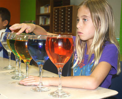 Cali Barker plays a melody on water glasses.