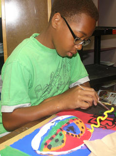 Le'Andre Brown concentrates as he paints.