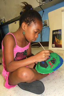 Paris Brown focuses intently while painting a mask.