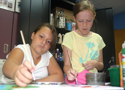 Briley Mudd and Gracie Bradshaw work together on a painting.