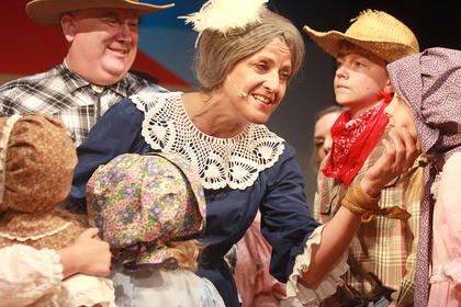 At the square dance, Aunt Eller (Suzanne Bennett) encourages farmers, ranchers and their children to get along.