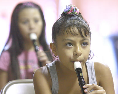 Judith Sandez, front, and Elaine Dominguez play the recorder during a music lesson.