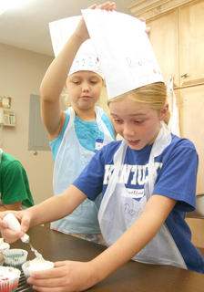 Sophie Thomas helps Brooklynne Bland with her chef's hat as Bland puts icing on a cupcake.