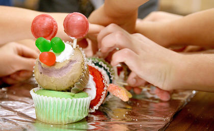 Culinary arts students work together to create a cupcake caterpillar.