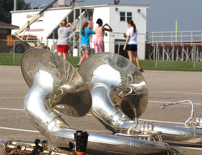 Two tubas lay glisten in the sun as members of the band practice in the background.