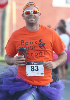 Stephen Peterson runs happily while wearing a purple tutu and drinking a McDonalds coffee during the Back Tutu School 2.2-mile Family Fun Run/Walk.
