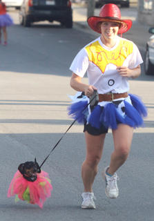 Taura Miles runs with dog Julie during the Back Tutu School 2.2-mile Family Fun Run/Walk.