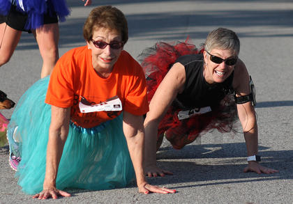 "Nancy Tatum, left, and Dawna Kelch drop to do some ""push-ups"" at the midway point of the Back Tutu School Run."