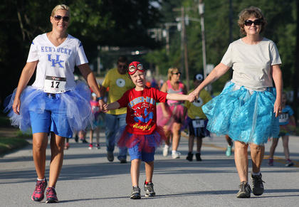 From left, Misty Lanz, Noah Lanz and Cabrini Gordon stick together as they complete the Back Tutu School Run course.