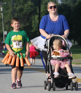 Ninja Turtle Braxton Benedict walks alongside his mom, Beth, and his sister, Emery.