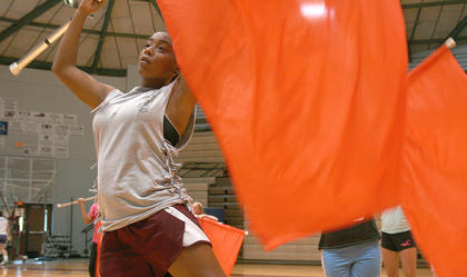 Junior Jarie Newby practices using the flag with the color guard.