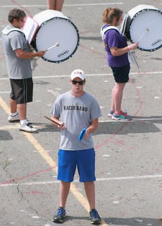 Instructor (and Marching Knights alumni) Trent Fenwick sets the pace, as junior Jordan Baize and sophomore Julia Davis play the bass drum.