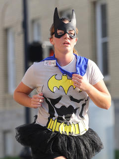 Abby Miles dons a Bat Girl costume while running past the post office on Main Street.