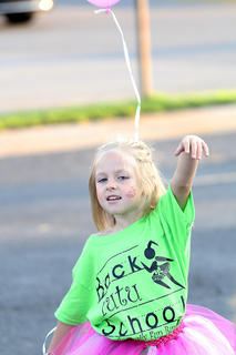 Music helped pump up many of the children before and during the event. Here, Pailee Conley dances with her balloon before the start of run/walk.