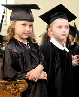 Katie Bradshaw, 4, slyly grins at the camera as she awaits her name being called to receive her diploma. Also pictured is 4-year-old Owen Thompson.
