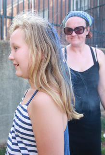 Madison Wise, 10, tries to stay still as Outreach Librarian Amanda Morgeson sprays her hair to give it a little color.