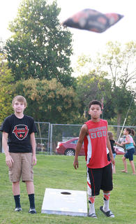 Devon Brown (left), 14, watches a throw by Dominick White, 11, during a game of cornhole.