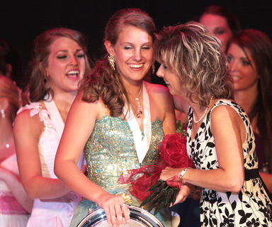 Paige Wilson, center, receives roses, a medal and a silver plate for being named Marion County Distinguished Young Woman. She also receives congratulations from reigning Kentucky Distinguished Young Woman Christine Mattingly (left) and Manette Young, Junior Miss co-chairwoman.