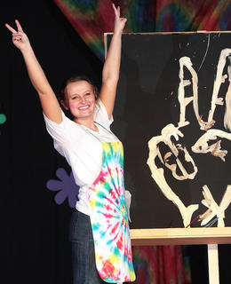 Anne Claire Thomas completes a speed painting demonstration during the Marion County Distinguished Young Woman competition to reveal a peace sign. This year's theme was the 1970s.