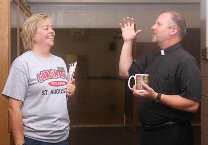 St. Augustine Principal Alicia Riggs chats with Rev. Bill Bowling after the students have headed off to their first classes of the school year.